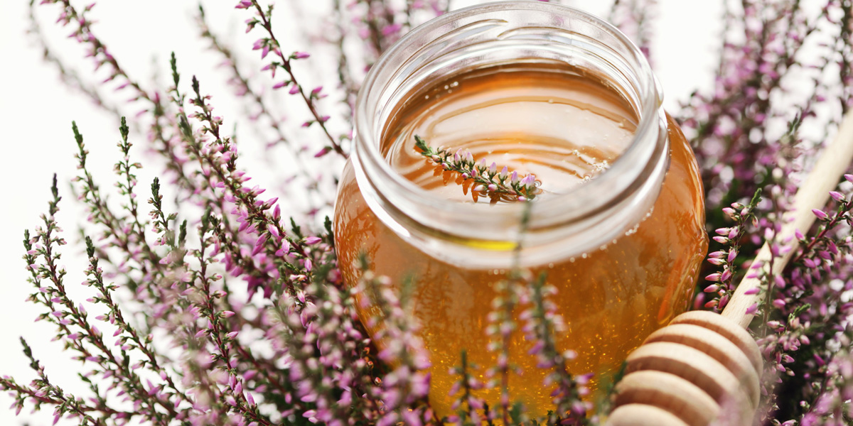 Heather honey in jar with fresh heather