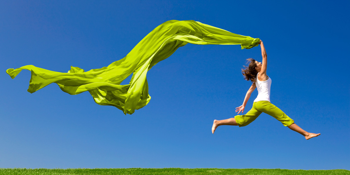 Beautiful young woman jumping on a green meadow