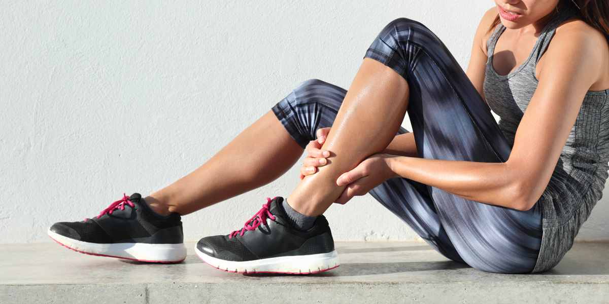 sports woman holding painful ankle