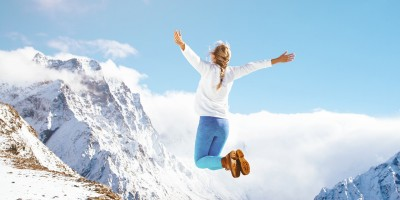 woman jumping on top of a mountain