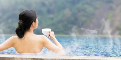woman relaxing in hot springs and drinking hot water