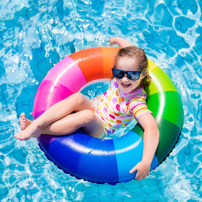 Girl on colourful ring in pool