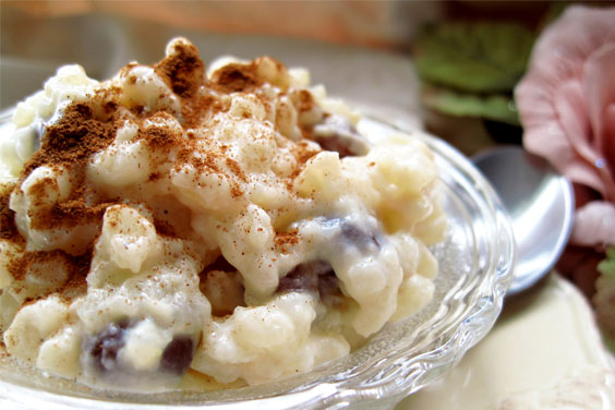 A rich and creamy rice pudding in a glass dish on plate. Cinnamon and raisins.